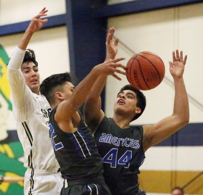 Esteban Fernandez, left, of Cathedral battles for a rebound with Christian Martinez, center, and JP Sanchez, 44, of Americas Tuesday night at Cathedral.