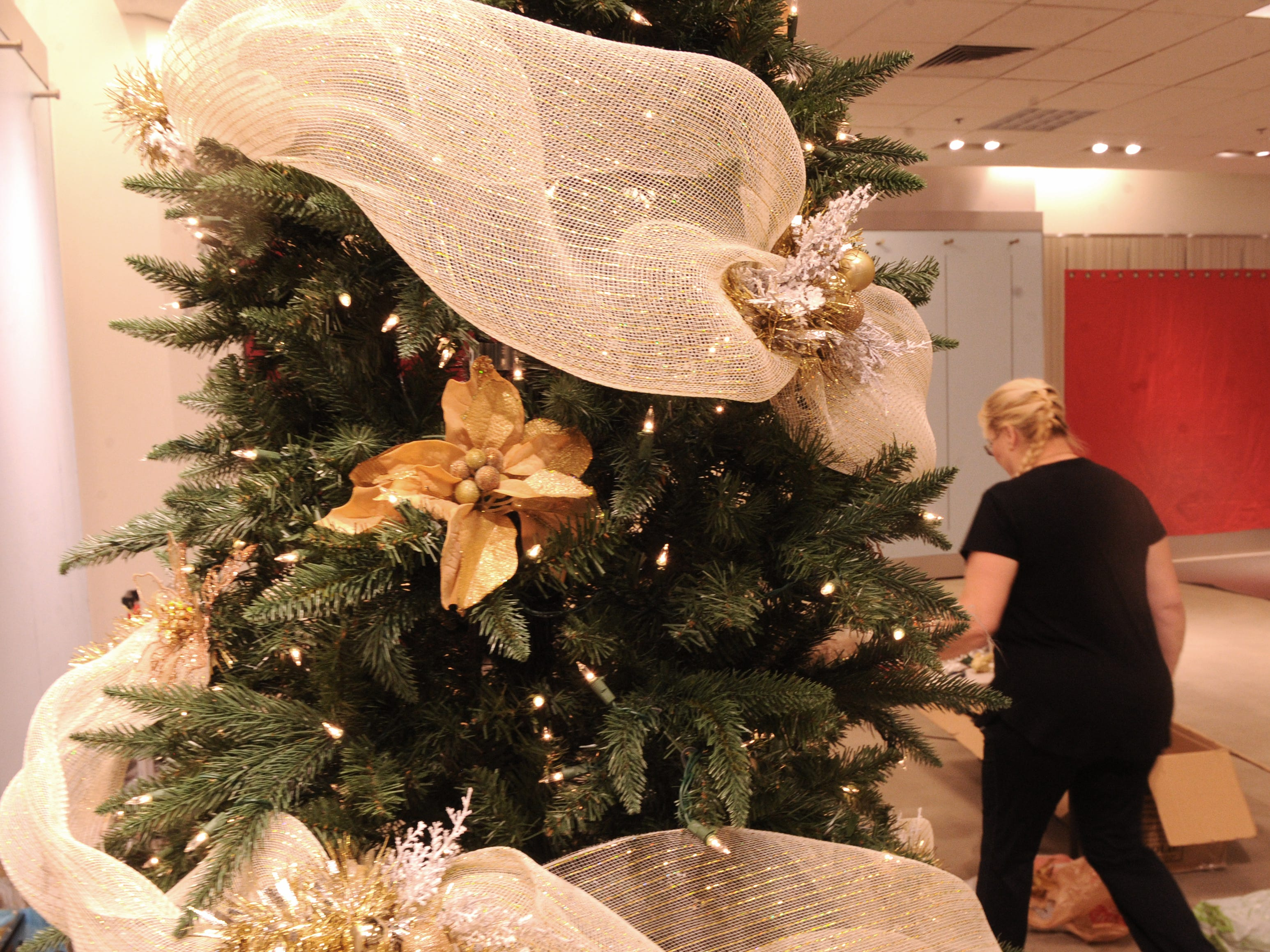 Laraine Yates walks behind her tree at the Simi Valley Festival of Trees. The event runs through Saturday in the old Macy's store at the east end of the Simi Valley Town Center mall.
