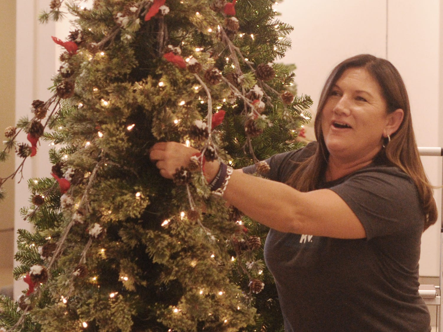 Debby Curry decorates her tree at the Simi Valley Festival of Trees. The event runs through Saturday in the old Macy's store at the east end of the Simi Valley Town Center mall.