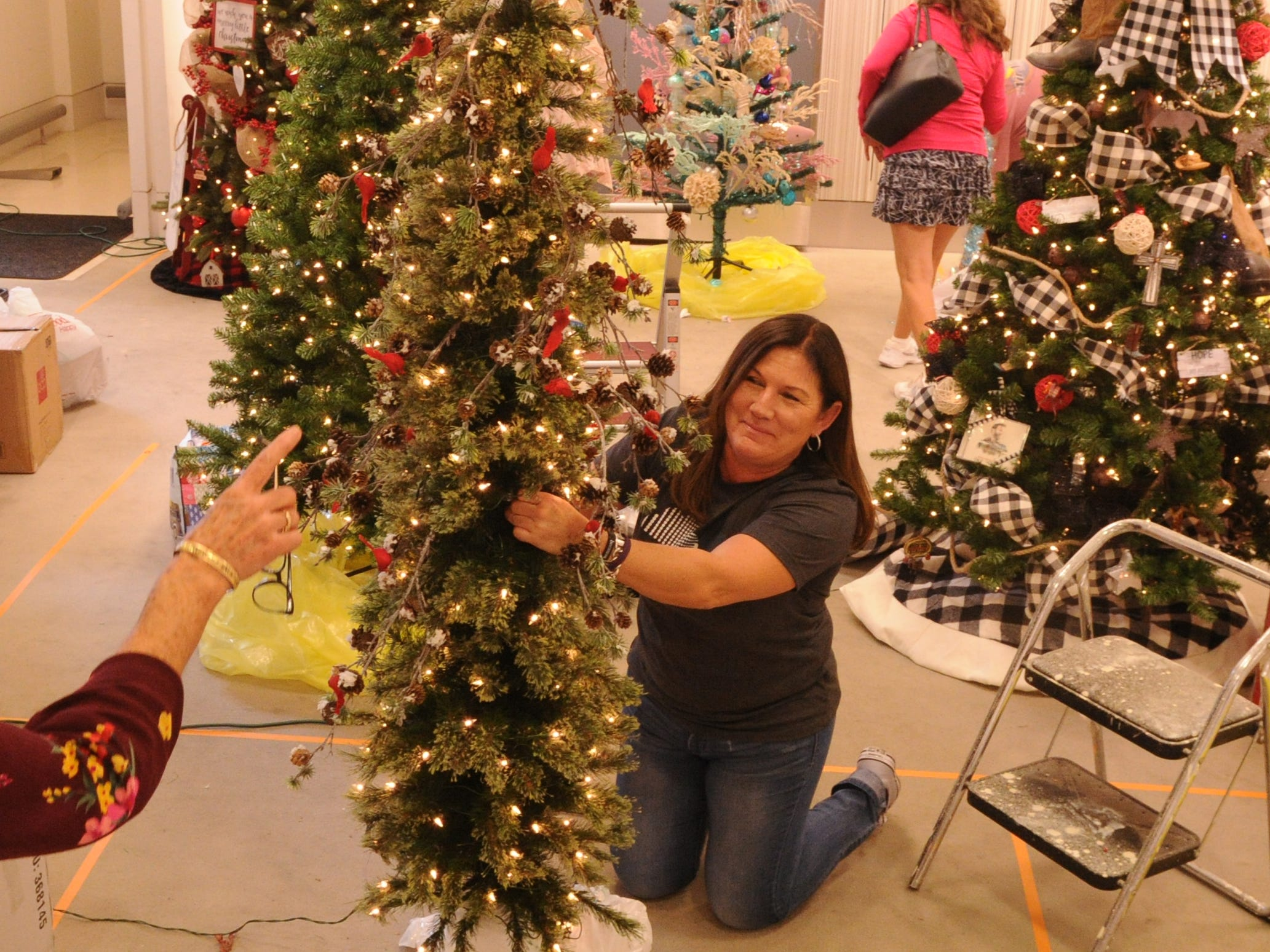 Debbie Curry decorates her tree at the Simi Valley Festival of Trees. The event runs through Saturday in the old Macy's store at the east end of the Simi Valley Town Center.