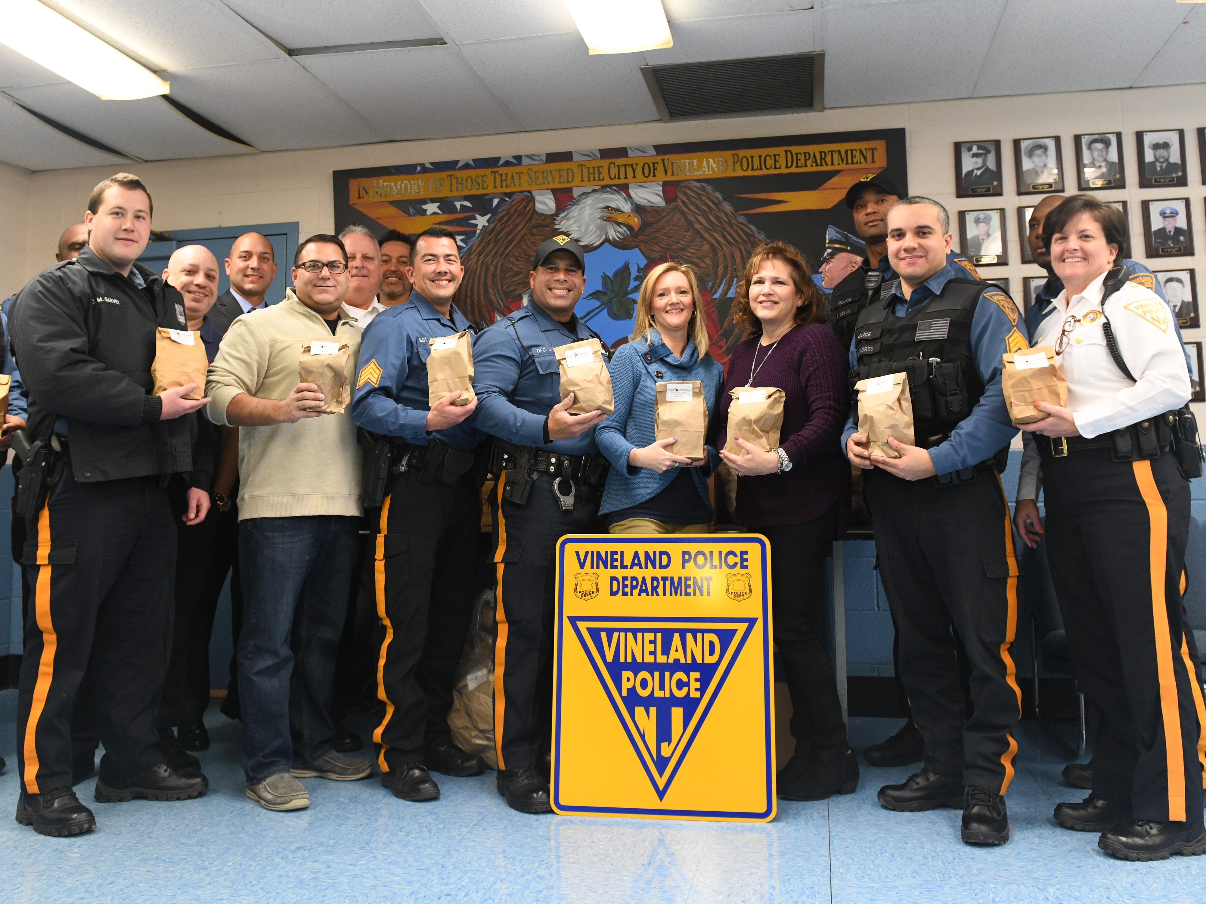 Members of the Vineland Police Department hold appreciation bags that were delivered by Volunteer Center of South Jersey staff members Maria Velez and Gabriella Smick on Wednesday, November 28, 2018.