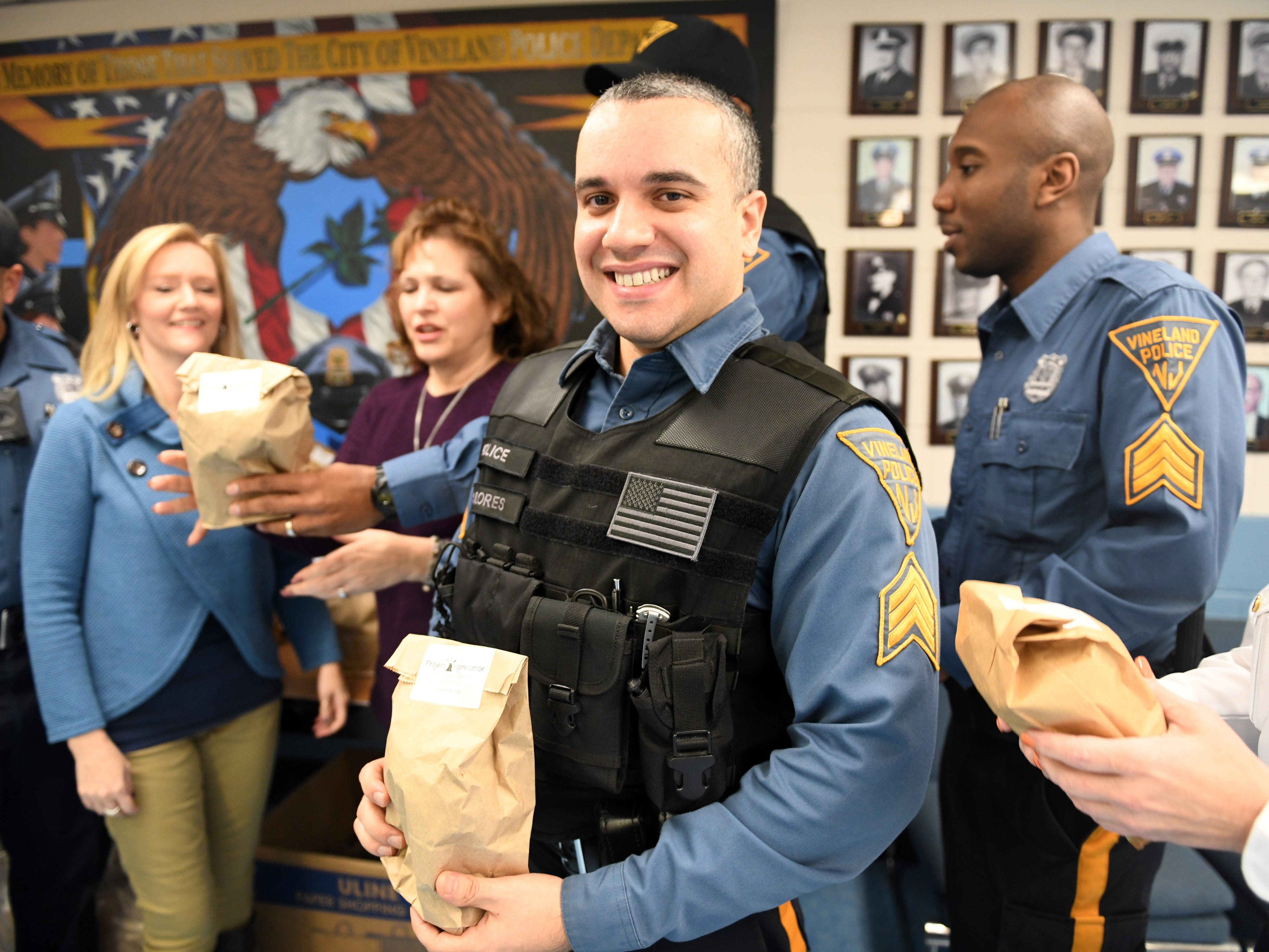 Sergeant Owen Flores holds a appreciation bag that was delivered by Volunteer Center of South Jersey staff members Maria Velez and Gabriella Smick on Wednesday, November 28, 2018.