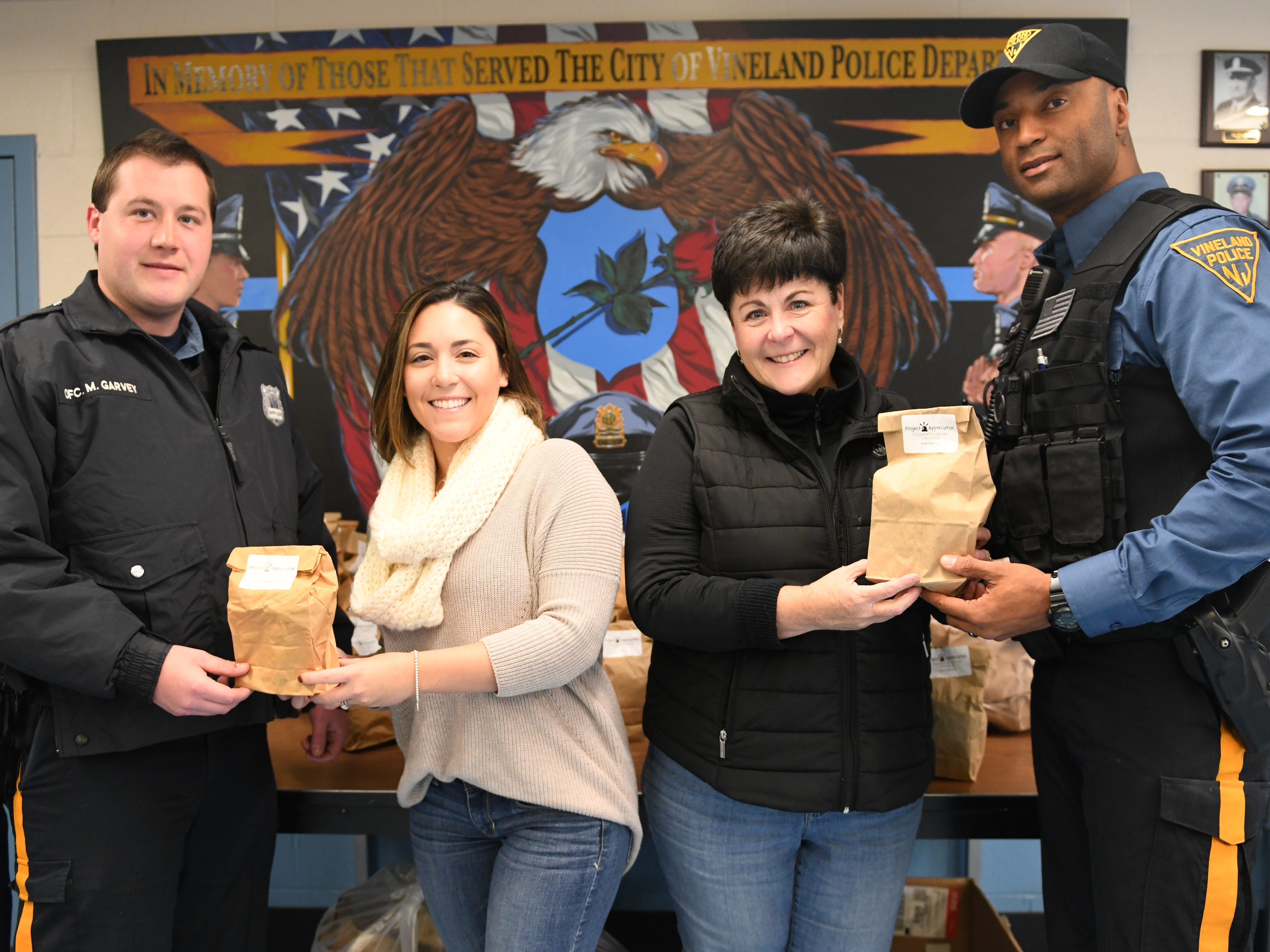 From left to right, Officer Matthew Garvey receives a appreciation bag from Volunteer Center of South Jersey staff member Gabriella Smick while Project Appreciation program coordinator Maria Velez gives Officer Dion Colvin a appreciation bag.