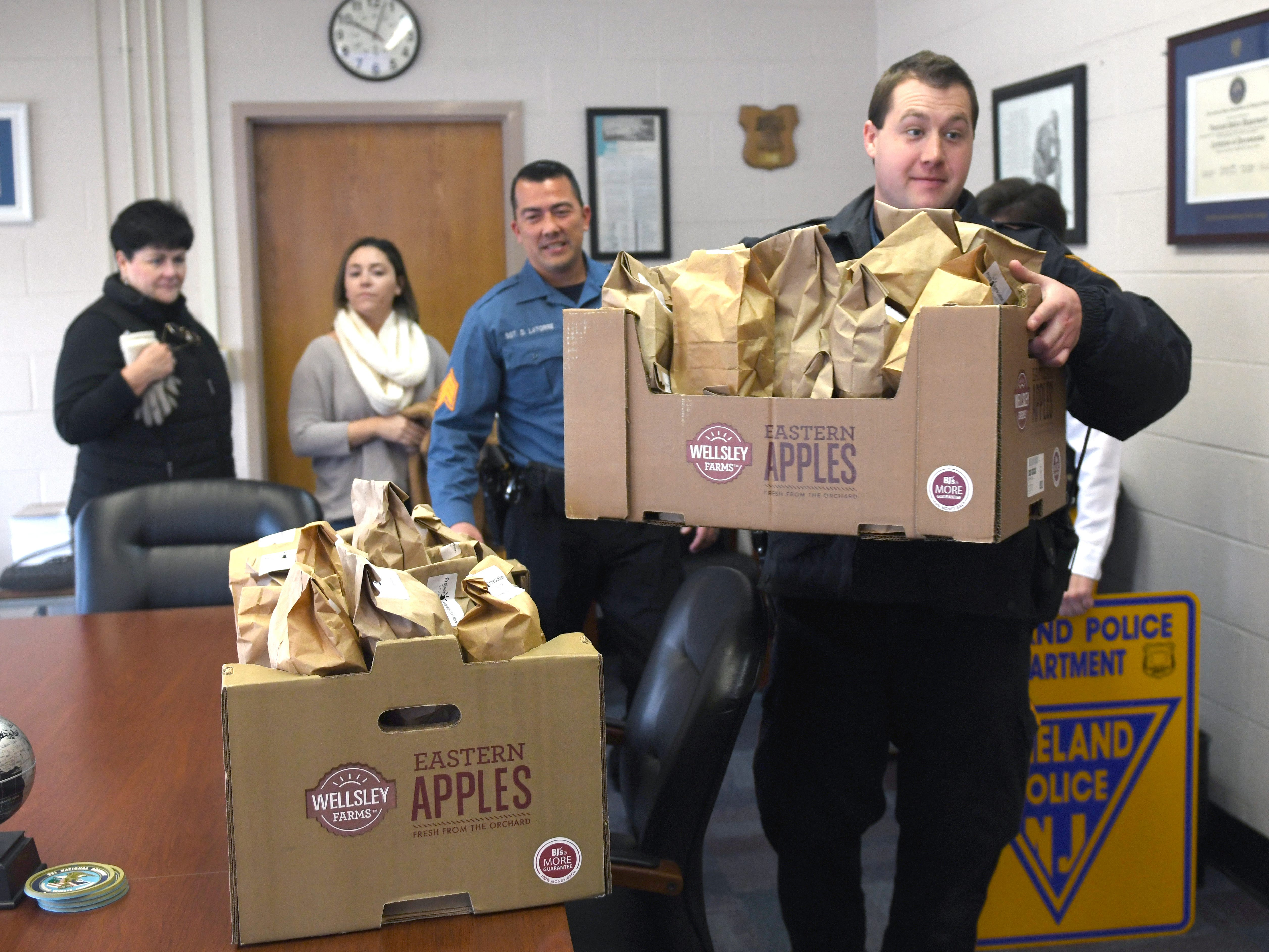 "Officer Matthew Garvey helps transport some of the appreciation bags delivered by members of the Volunteer Center of South Jersey. The ""thank you"" bags contain a variety of items such as a coffee pod, power bar, cough drops, napkins, hand sanitizer and more."
