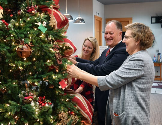 Crystal Sullivan, left, and Susan Pacanowski, supervisors with Adult Protective Services, and John Buckley, president of Texoma Community Credit Union, add ornaments to the Tree of Life Wednesday.