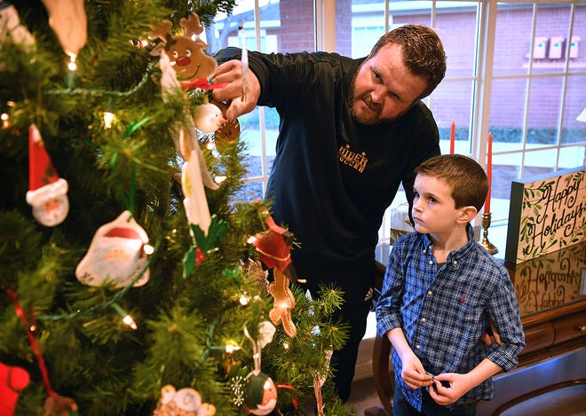 Jackson Holly, 6, and his father, Dustin Holly, look over a Christmas tree at Hospice of Wichita Falls. Dustin Holly's mother, Pam Pitts, was a patient at Hospice in November 2013.