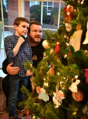 Dustin Holly and his son, Jackson Holly, check out the Christmas tree at Hospice of Wichita Falls. Hospice took care of Dustin's mother, Pam Pitts, in 2013 and the Tree of Lights on the Chase bank tower has always held special meaning for him.
