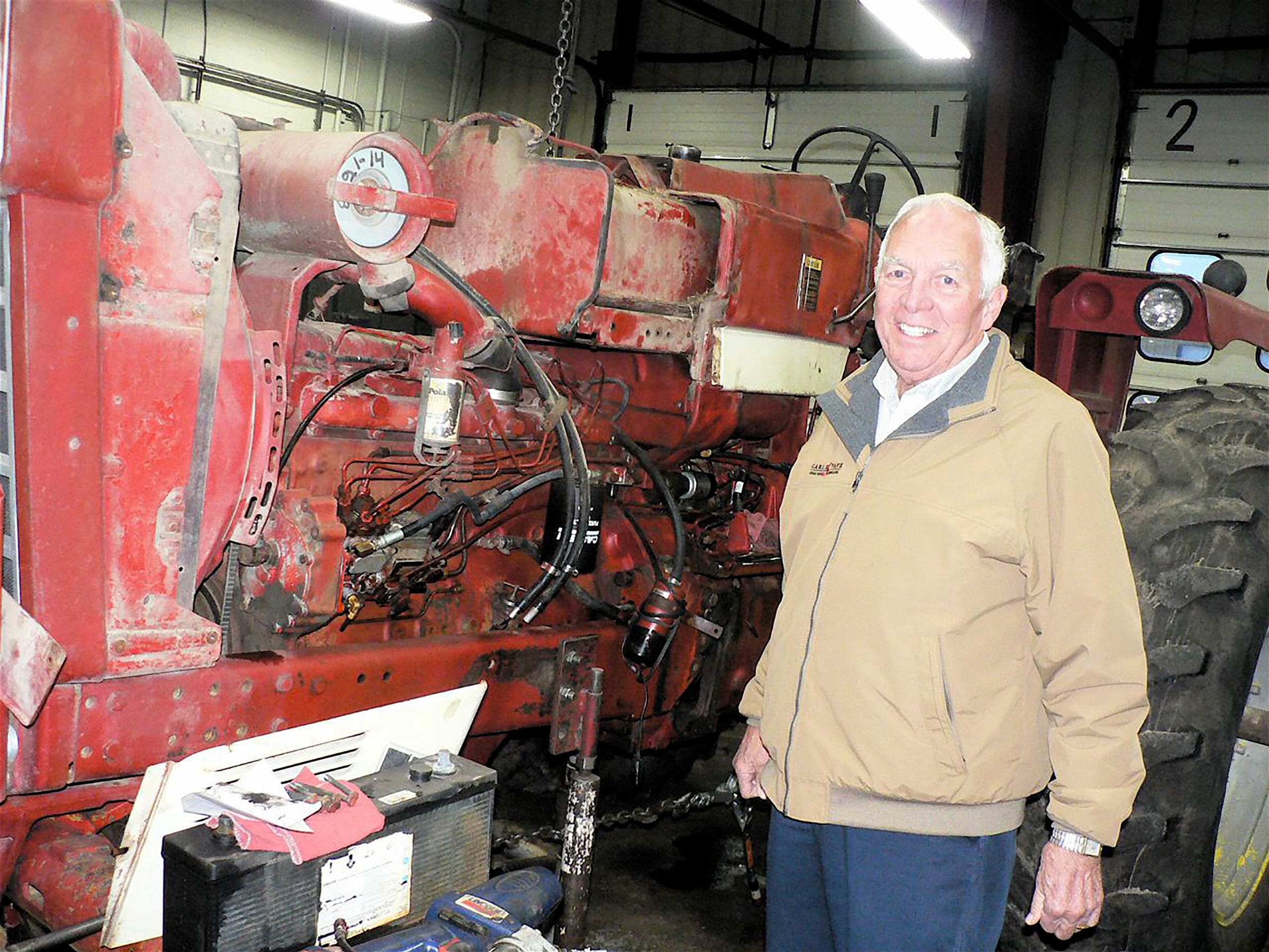Ken Statz and a 1970s Farmall that is in three pieces while being repaired.