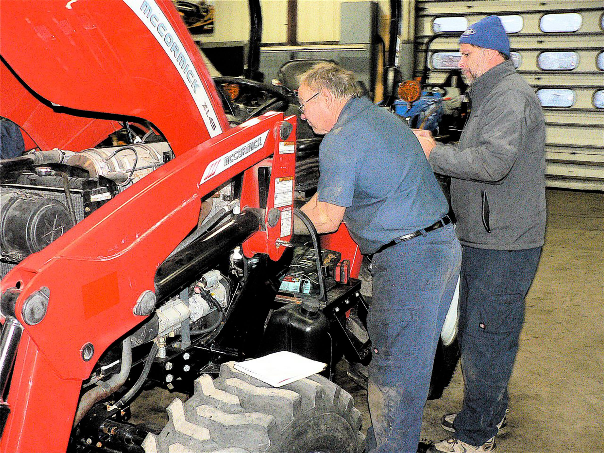 Ken Davidson and Steve Wambold working on a tractor.