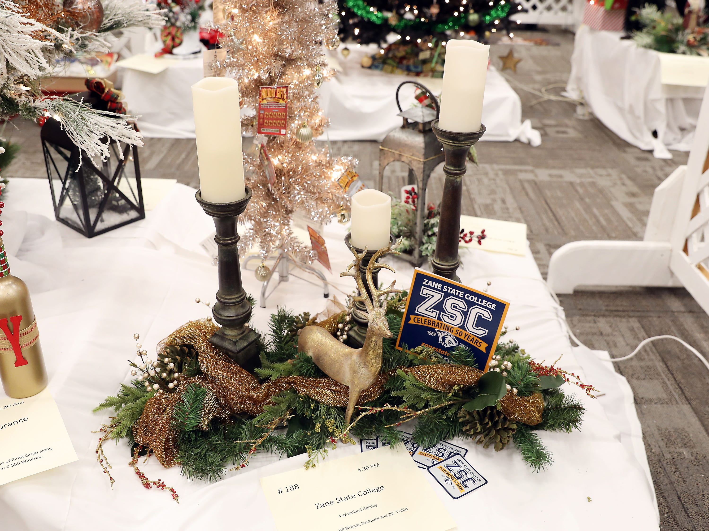 1884:30 PMZane State CollegeCenterpieceA Woodland HolidayBeautiful centerpiece for your holiday table.  Includes three tiered candlesticks, remote control candles, pine garland and bronze deer.HP Stream, backpack and ZSC T-shirt