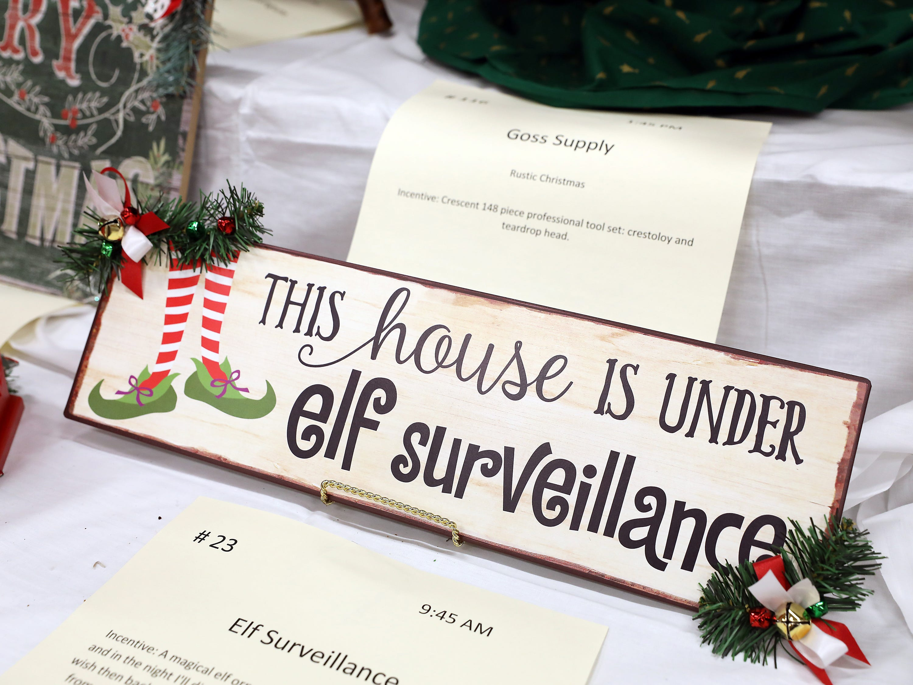 "23	9:45 AM	Committee Entry	Other	Elf Surveillance	""This house is under elf surveillance"" 20""x6"" metal sign adorned with green pine and jingle bells		A magical elf ornament - ""Whisper a wish into my ear and in the night I'll disappear.  I'll fly to see santa and tell him the wish then back to your home with a magical swish.  If I'm not back from where I have been find me and a wish you'll win.  How to Catch an Elf children's book from the New York Times bestselling team Adam Wallace and Andy Elkerton"