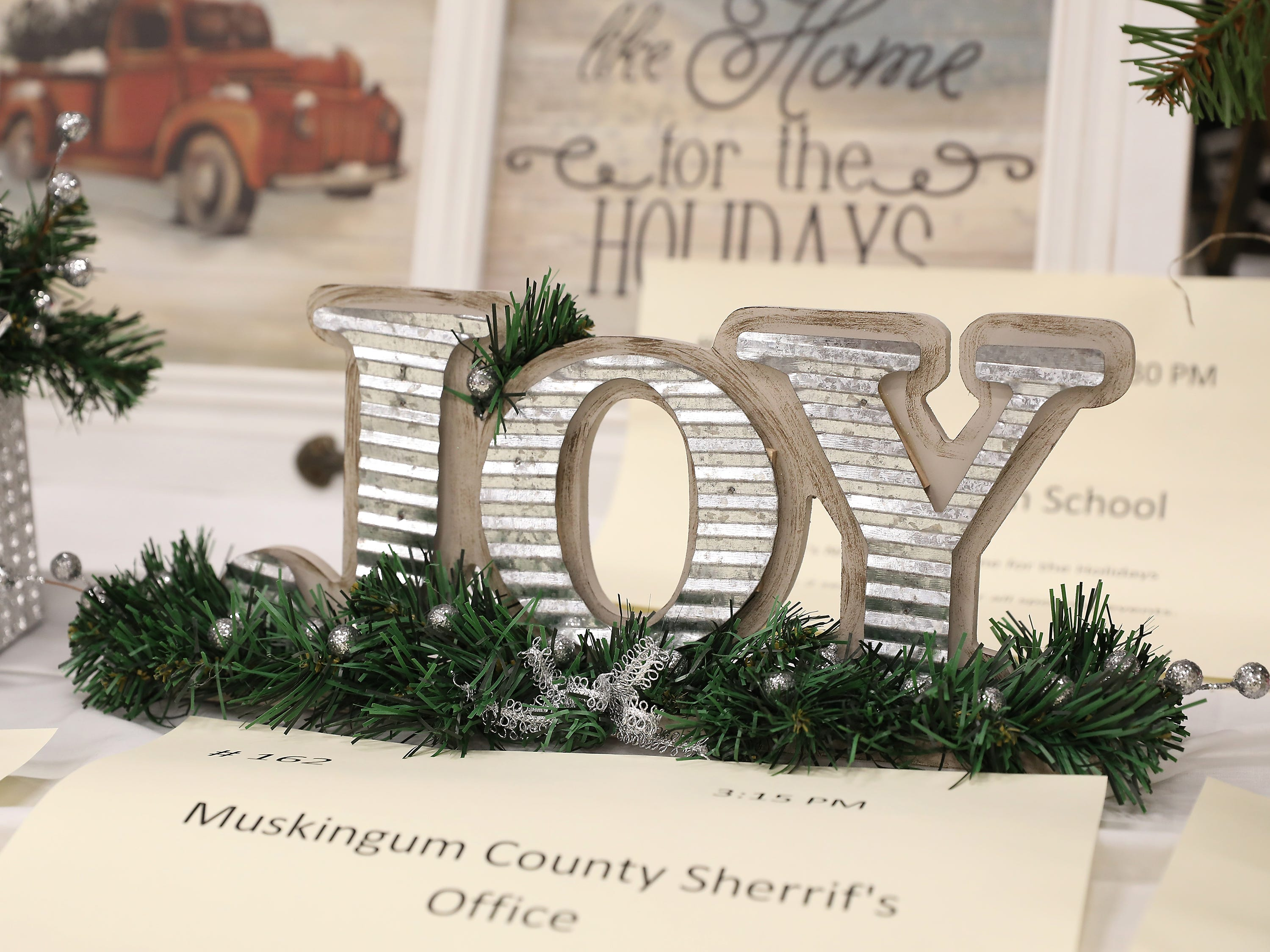 """1623:15 PMMuskingum County Sherrif's OfficeOtherFarmhouse JoyA farmhouse country Christmas joy tabletop accent featuring corrugated metal spelling out """"Joy"""" with pine and red berries to add a burst of color!  Let your holidays be filled with Joy.K-9 Ride to School"""