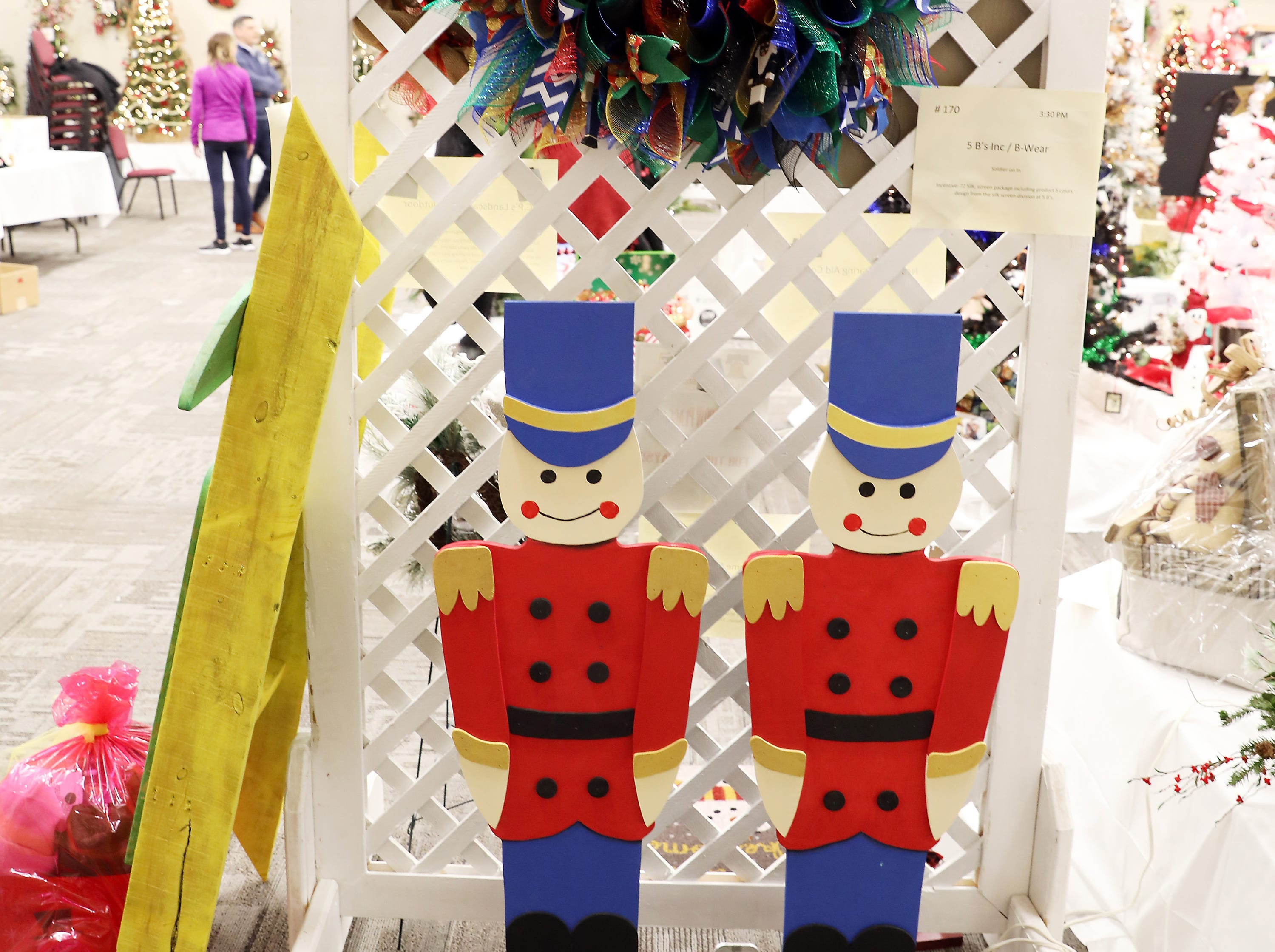 """1703:30 PM5 B's Inc / B-WearWreathSoldier on In28"""" multi color deco wreath with Merry Christmas Center.  Two 48"""" tall wooden toy soldiers painted bright blue, red and gold.  Black boot and hat with bright gold band.  Can be set by your door, fireplace etc.72 Silk, screen package including product 5 colors design from the silk screen division at 5 B's."""