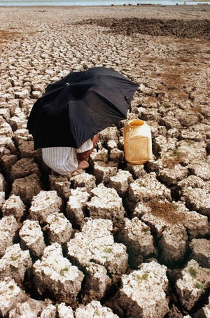 "A man shades himself from the sun with an umbrella as he takes a break from walking across the dry bed of the Upper Lake in Bhopal, India, on May 20, 2002. Extreme heat because of climate change is a ""medical emergency,"" experts say."