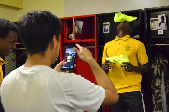"Michael Chavez, 17, takes a photo of fellow reVision FC player Amani ""Fufu"" Kwizera, 17, to post on Instagram."