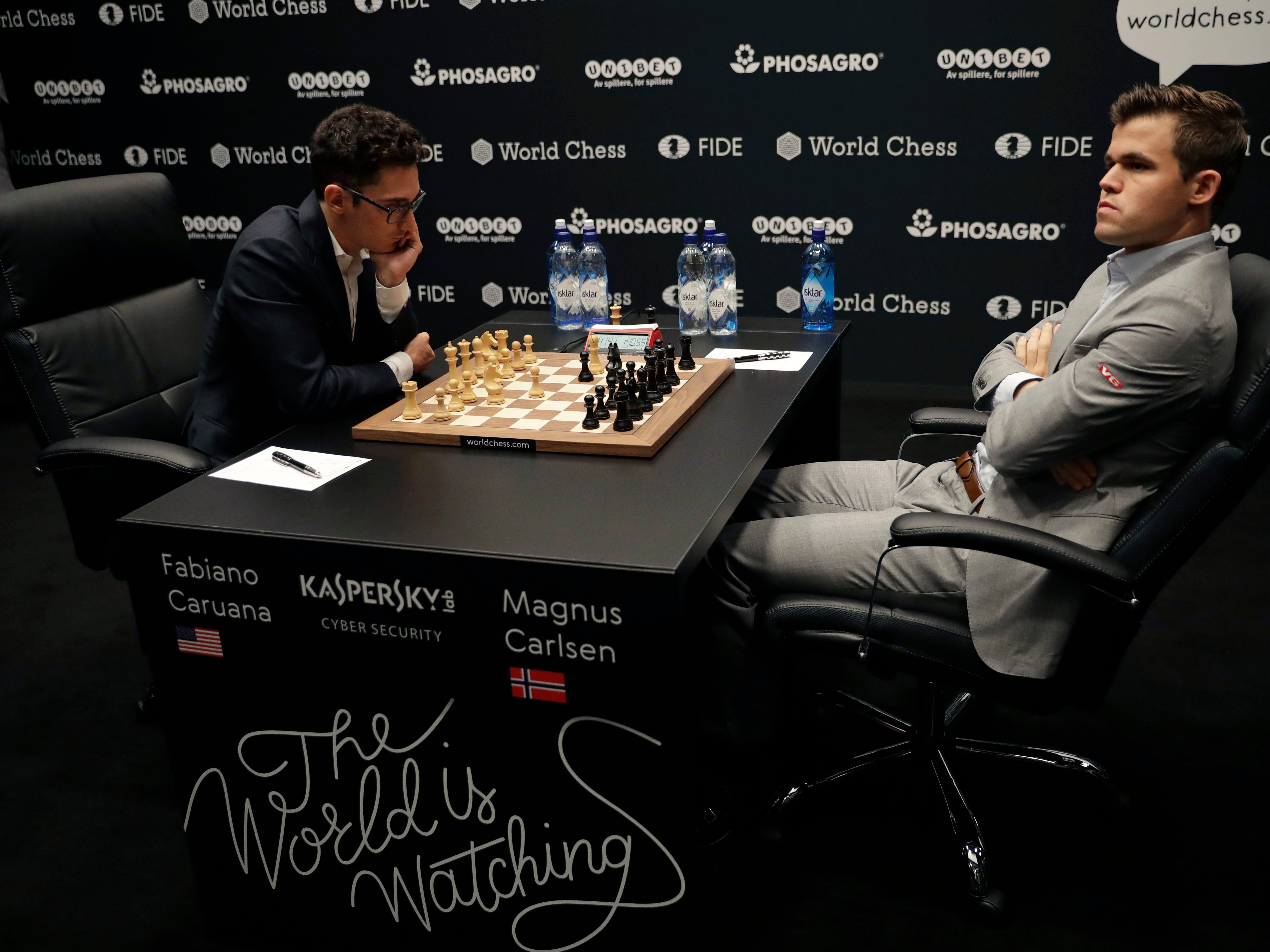 Reigning chess world champion Magnus Carlsen, right, from Norway, plays Italian-American challenger Fabiano Caruana in the first five minutes of round three of their World Chess Championship Match in London, Monday, Nov.  12, 2018.