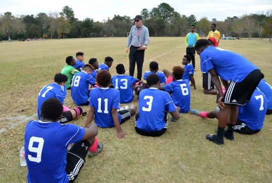 Coach Charles Rotramel gives his reVision FC players a pep talk during half-time of a big game in Houston.