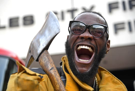 Deontay Wilder lets out a yell as he holds a firefighter's ax on his visit to Los Angeles County Fire Department Station 3 during the lead up to his heavyweight fight against Tyson Fury Saturday at the The Forum.