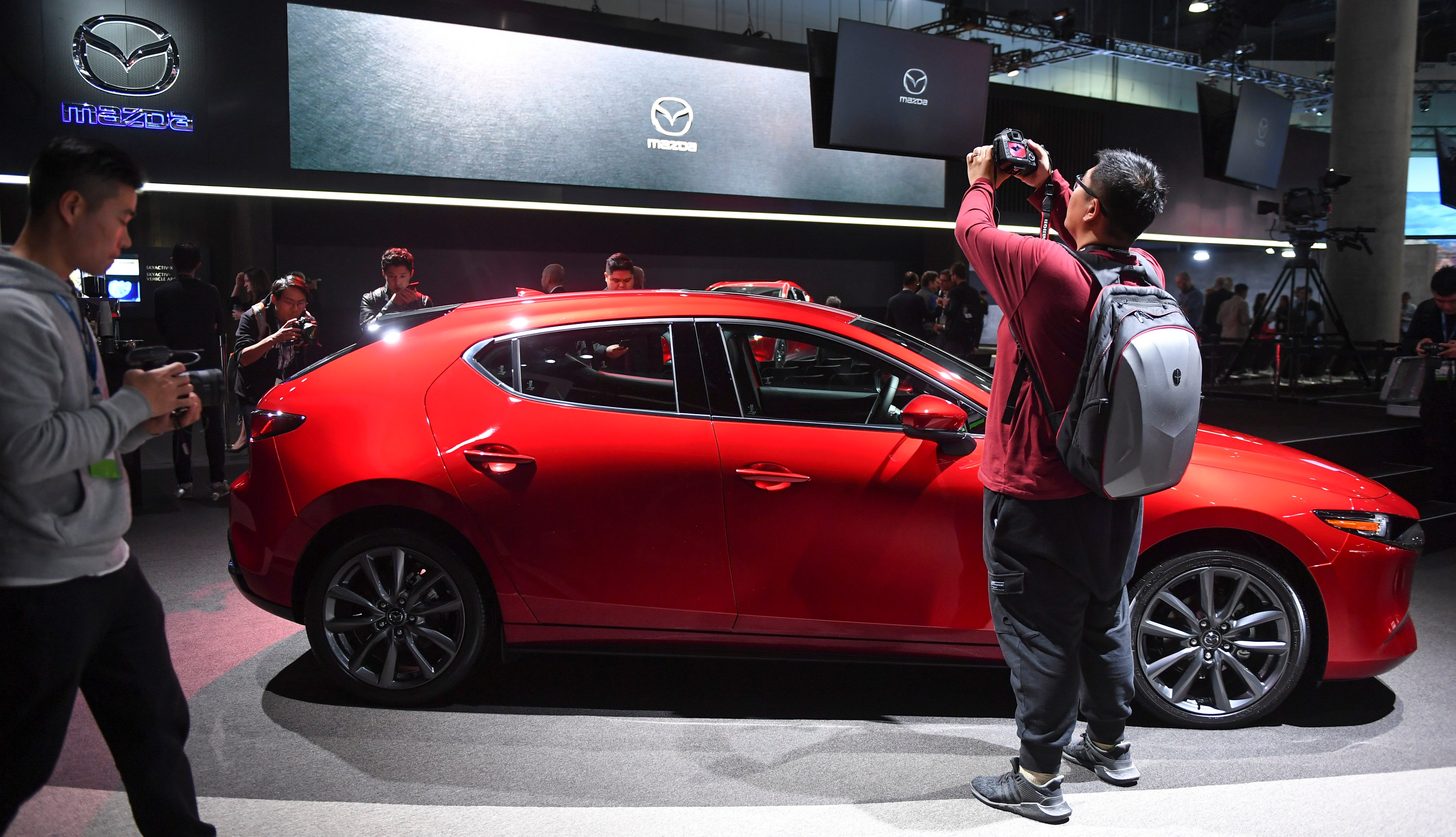 The Mazda 3 draws a crowd of photographers during press preview day at Los Angeles Auto Show.