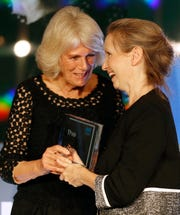 """Camilla, Duchess of Cornwall, presents """"Milkman"""" author Anna Burns with the Man Booker Prize for Fiction on Oct. 16, 2018 in London."""