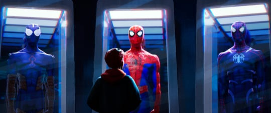 """Miles Morales (voiced by Shameik Moore) looks on in awe at his idol's supersuits in """"Spider-Man: Into the Spider-Verse."""""""