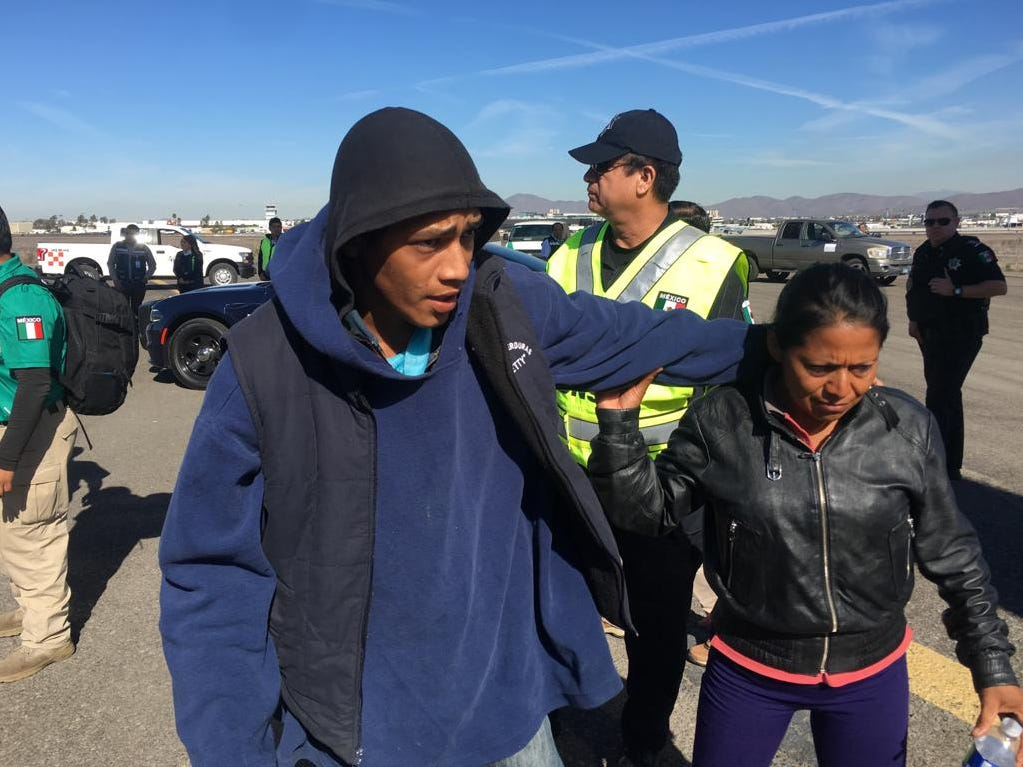 Honduran migrants are escorted to a Mexican Federal Police airplane in Tijuana, Mexico that is headed to Mexico City where they will be processed for repatriation to Honduras on Nov. 27, 2018. The migrants were part of the migrant caravan that arrived in the city of Tijuana, Mexico but decided to voluntarily return to their country.