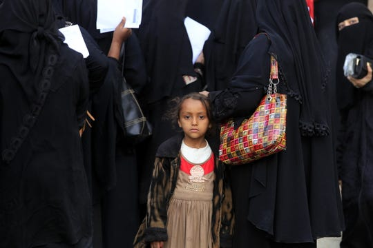 A Yemeni child stands with displaced people gathering to register at an evacuation center after fleeing home due to ongoing conflict, in Sana'a, Yemen, Nov. 17, 2018.