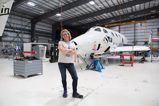 Australian Vivien Cornish, shown here during a visit to Virgin Galactic's Mojave headquarters, is among 600 space fans who have paid $250,000 for a ride on SpaceShipTwo, shown behind Cornish.