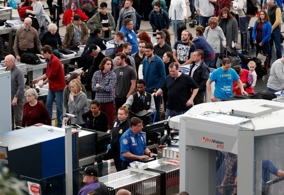 Travelers wait in long lines to pass through a security checkpoint in Denver International Airport on Wednesday, Nov. 21, 2018.