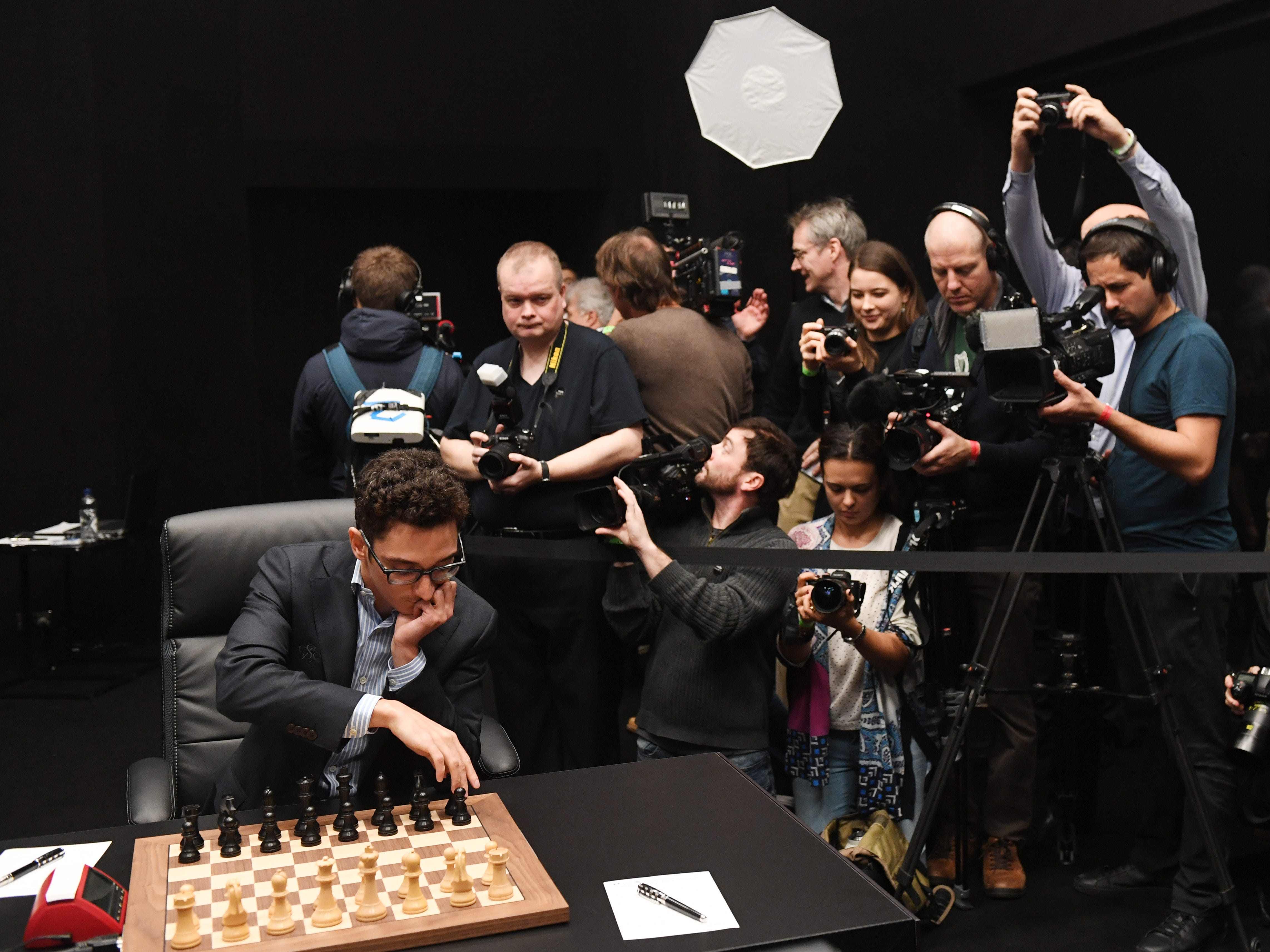 American challenger Fabiano Caruana, left, arranges the board before playing against  reigning chess world champion Magnus Carlsen in their round 11 game during the World Chess Championship, Nov. 24, 2018, in London.