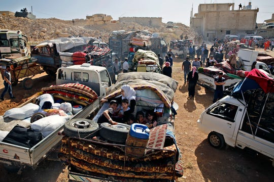 Syrian refugees gather in their vehicles getting ready to cross into Syria from the eastern Lebanese border town of Arsal, Lebanon.