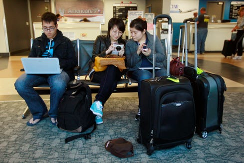 Sam Liao, Jill Lin, and Alice Gu, all 22, and international students at Millikin University in Decatur, Ill., are stranded March 12, 2012, at the Abraham Lincoln Airport in Springfield, Ill., when the DirectAir flight taking them to Florida for spring break was cancelled.
