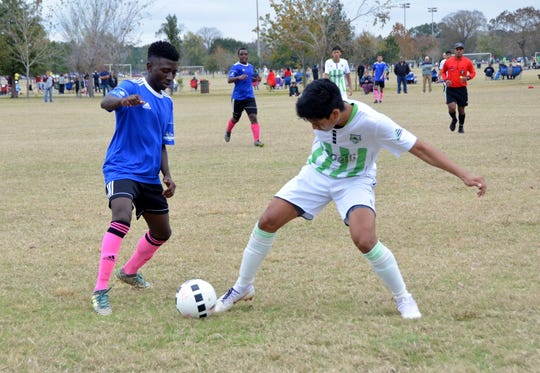 Iluta Shabani, 17, a reVision FC player, tussles for the ball with a player from the Cedar Stars Academy-Green team.