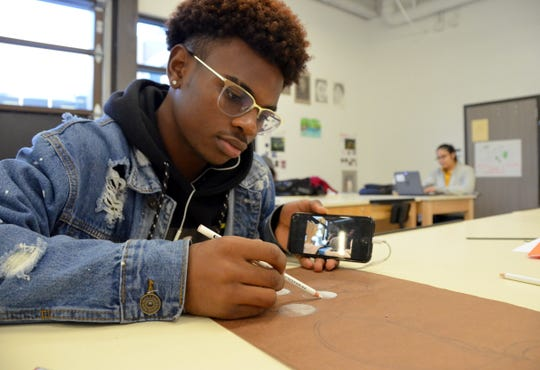 Amani Godfrey, 18, a reVision FC player, works on a drawing at Houston's Margaret Long Wisdom High School, where refugee students come from 29 different countries.