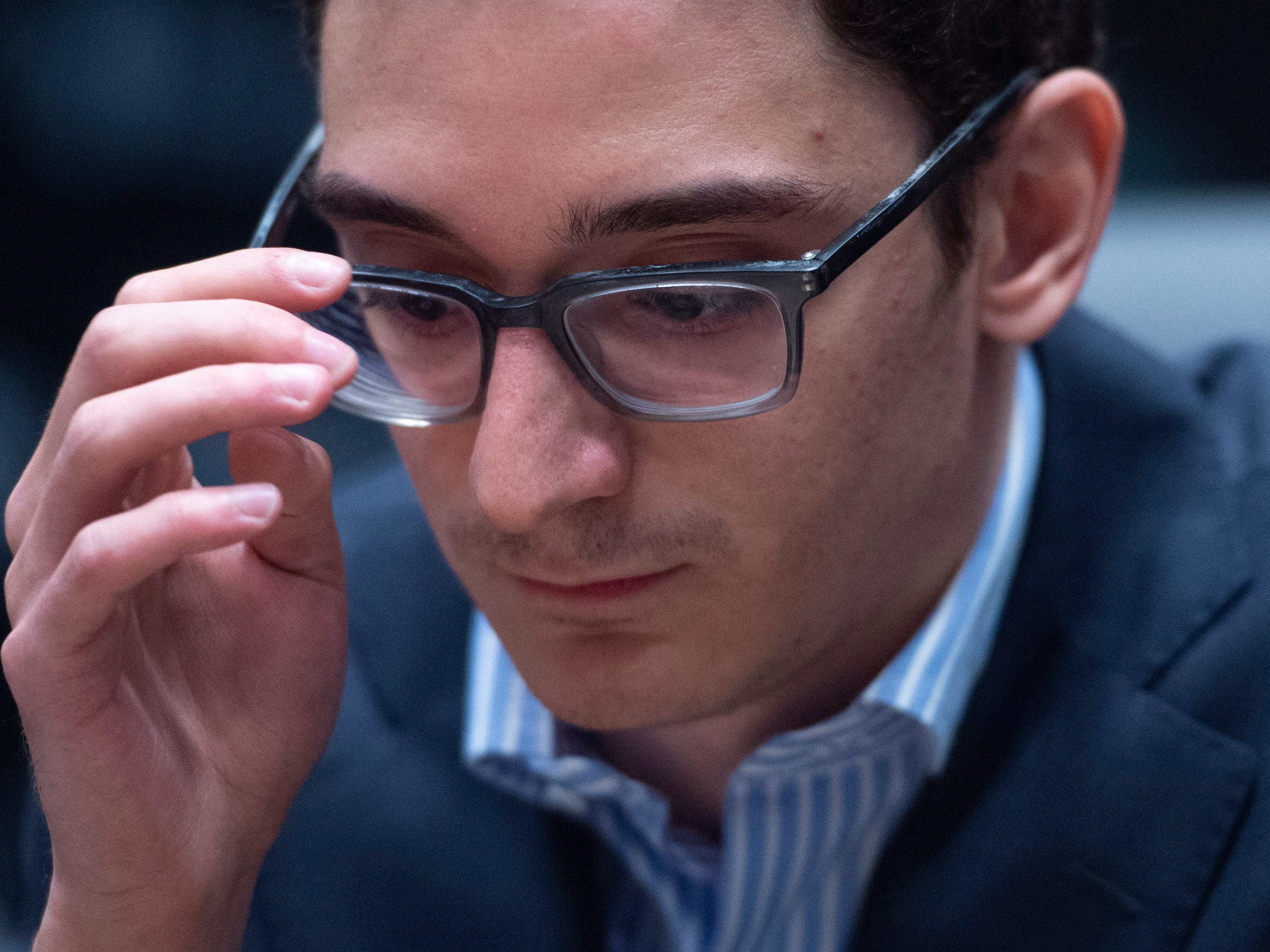 American Fabiano Caruana contemplates his next move against reigning chess world champion Magnus Carlsen in their round eleven game during the World Chess Championship, Nov. 24, 2018, in London.