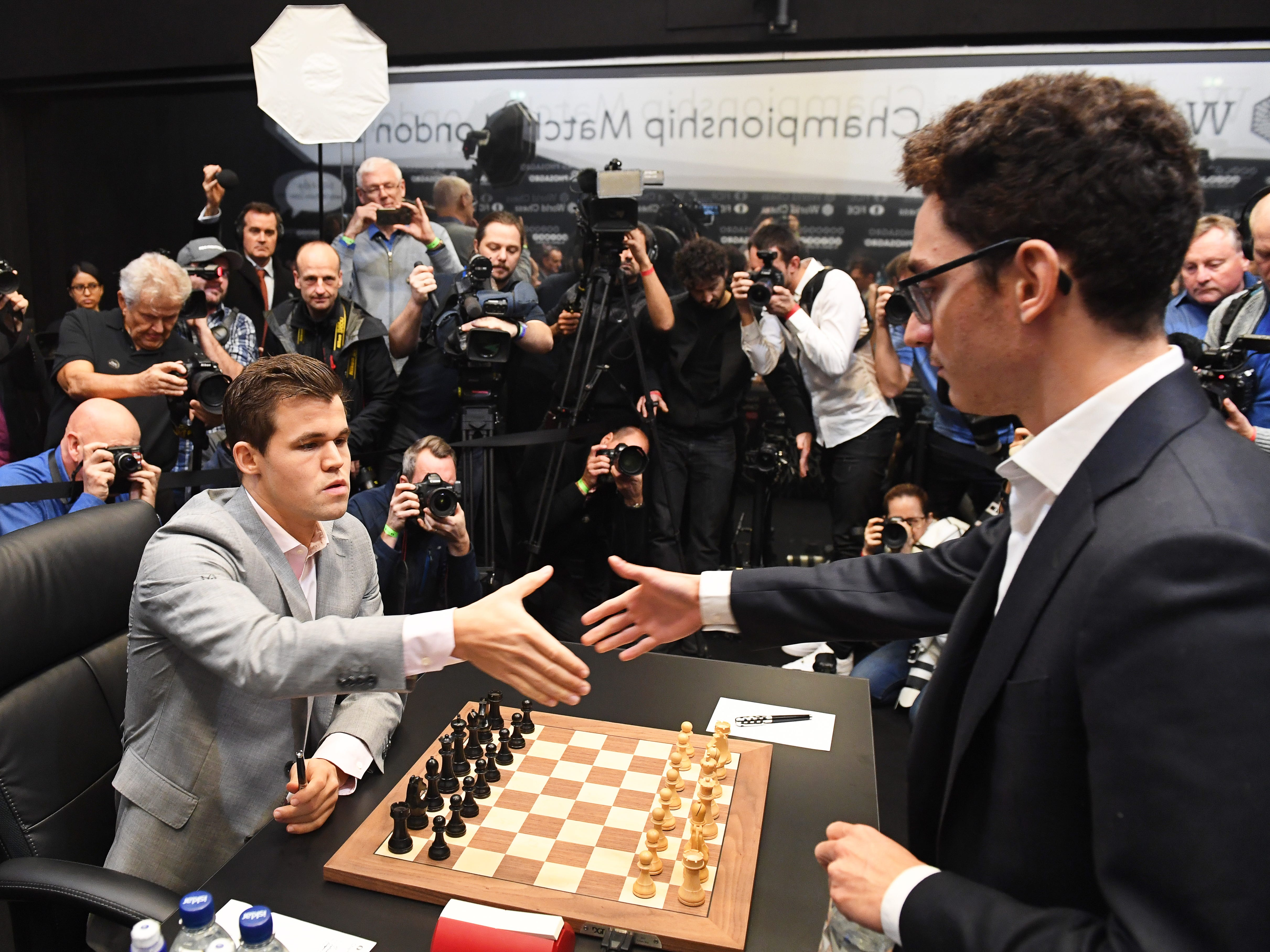Reigning chess world champion Magnus Carlsen, left, shake hands with American challenger Fabiano Caruana before their round 12 game during their World Chess Championship, Nov. 26, 2018, in London.