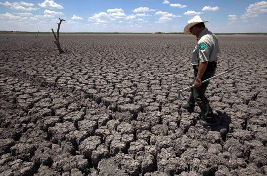 Texas State Park police officer Thomas Bigham walks across the cracked lake bed of O.C. Fisher Lake in San Angelo, Texas, in August 2011. A new study suggests that the double-whammy of heat and drought is growing more frequent due to climate change.