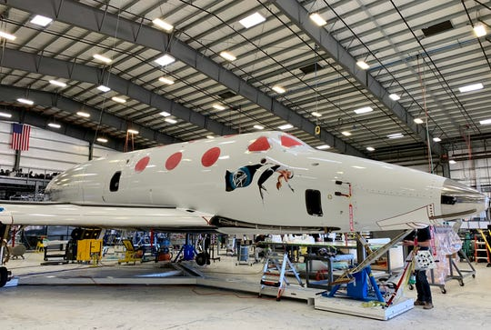 "Virgin Galactic's SpaceShipTwo, also known as VSS Unity, undergoes checks before its next test flight at the company's private facility in Mojave, Calif. The illustration of the woman floating in space on the fuselage is said to be drawn from a youthful photo of founder Richard Branson's mother, Eve. The spaceship looks like a cross between a Gulfstream jet and something out of ""Star Trek."""