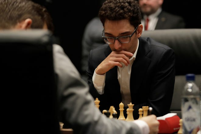 Italian-American challenger Fabiano Caruana plays reigning chess world champion Magnus Carlsen, left, from Norway, in the first few minutes of round 12 of their World Chess Championship Match in London, Monday, Nov. 26, 2018.