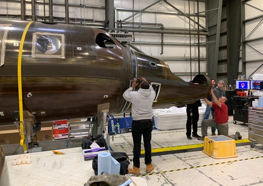 Virgin Galactic engineers work on one of two more SpaceShipTwo crafts that are in progress at the company's headquarters in Mojave, Calif. Eventually, the company hopes to have as many as six spaceships, which could theoretically allow for multiple flights a week into space.