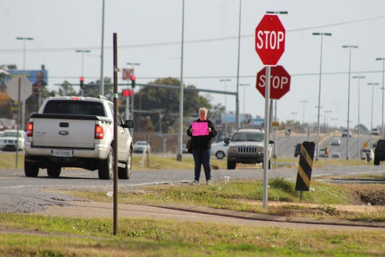 A woman holding a sign stands on the MacArthur Drive service road Wednesday. A few minutes later, a passenger in a Dodge Challenger handed her some cash.