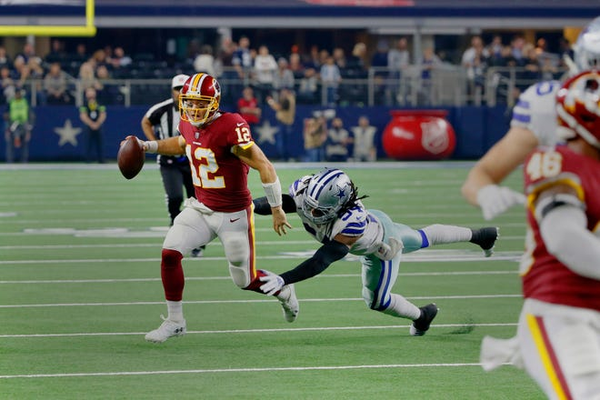 Washington Redskins quarterback Colt McCoy (12) tries to avoid a tackle by Dallas Cowboys linebacker Jaylon Smith (54) during the second half in Arlington, Texas, Thursday, Nov. 22, 2018. The Dallas Cowboys won 31-23.
