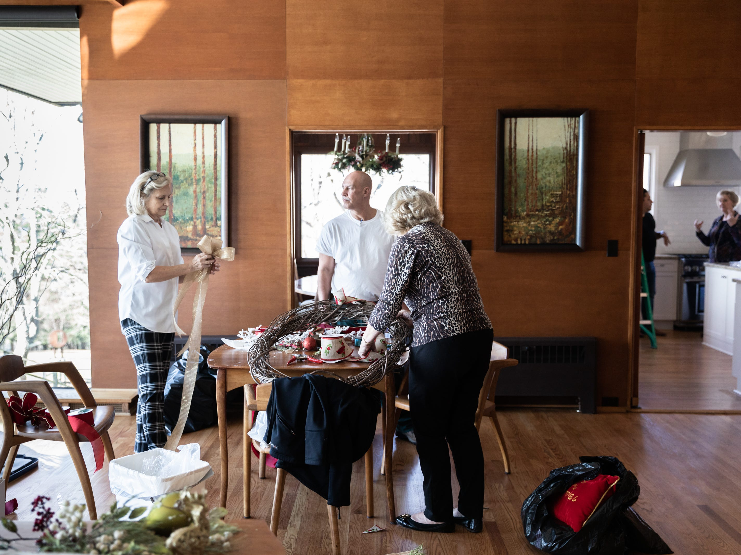 Kaye Myers, of Asheville, Tony Hartsell, of Asheville and June Ray, of Waynesville, members of the Governor's Western Residence Board of Directors, work on assembling decorations for the holidays at the residence, Nov. 29, 2018.