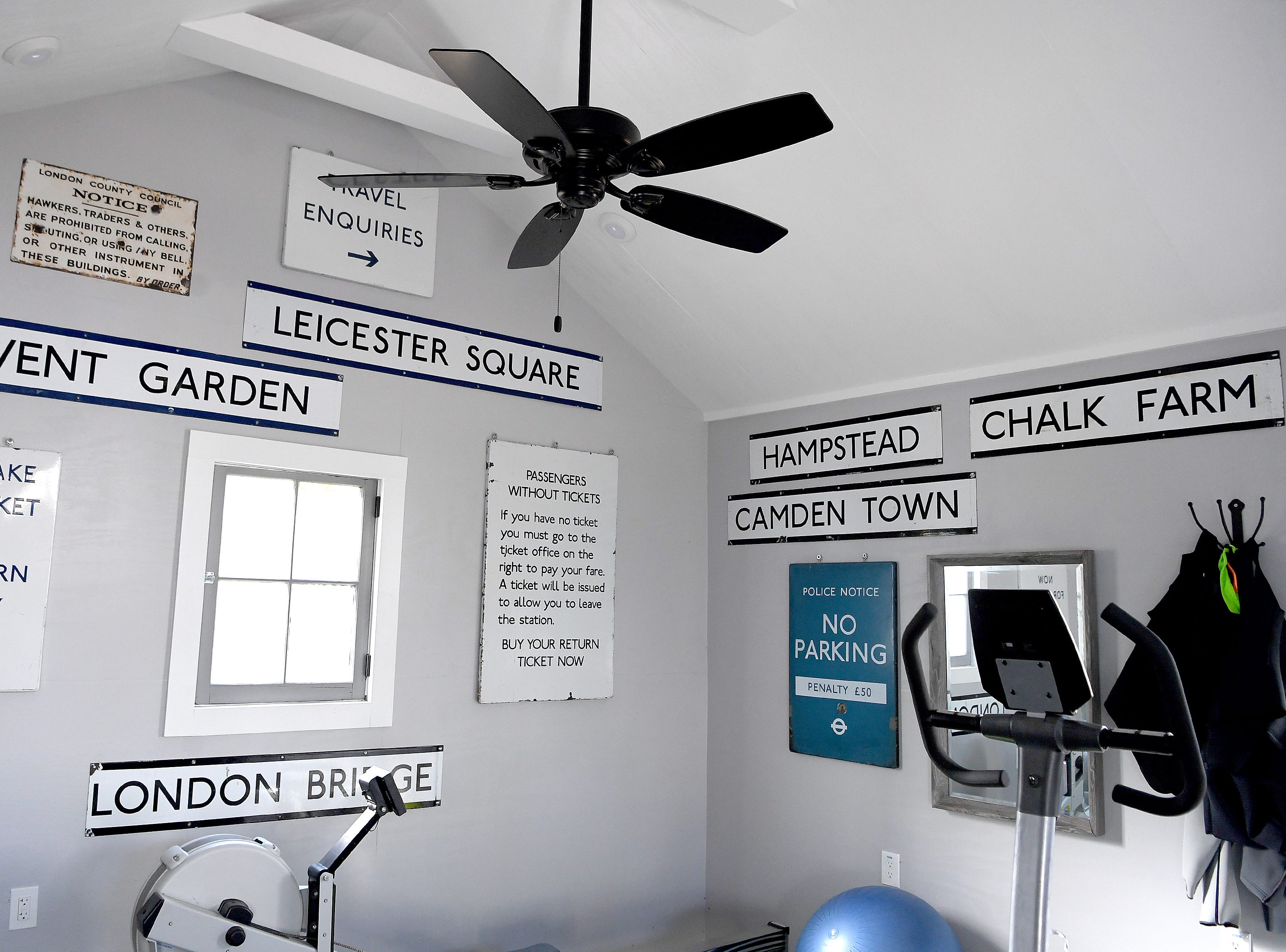 London road signs bought at an auction when Linda and Marc Voorhees lived abroad are displayed in their detached garage which they use as an exercise room.