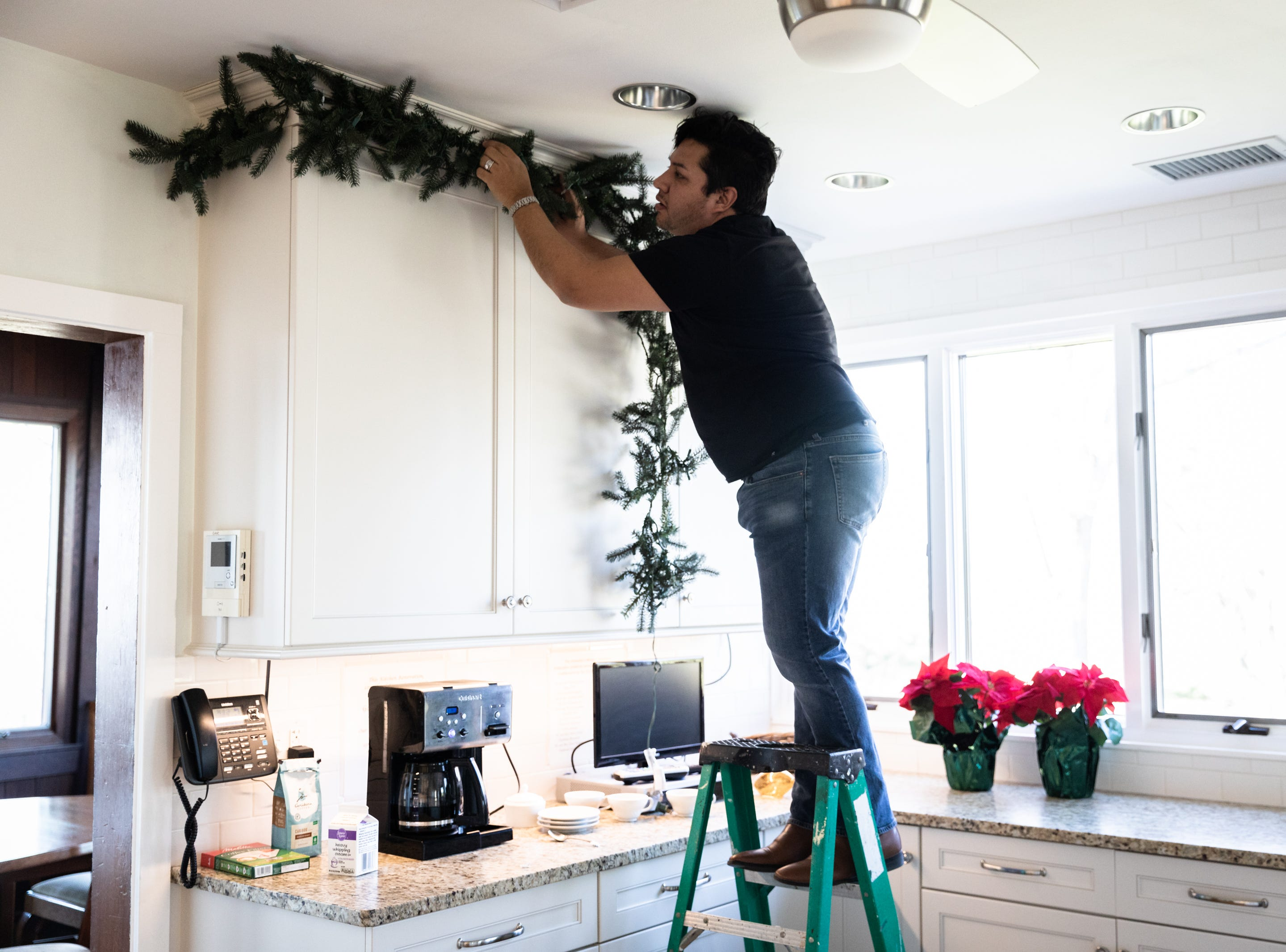 Yona Wade, of the Eastern Band of Cherokee Indians, a member of the Governor's Western Residence Board of Directors, decorates the kitchen for the holidays at the residence on Patton Mountain Road, Nov. 29, 2018.