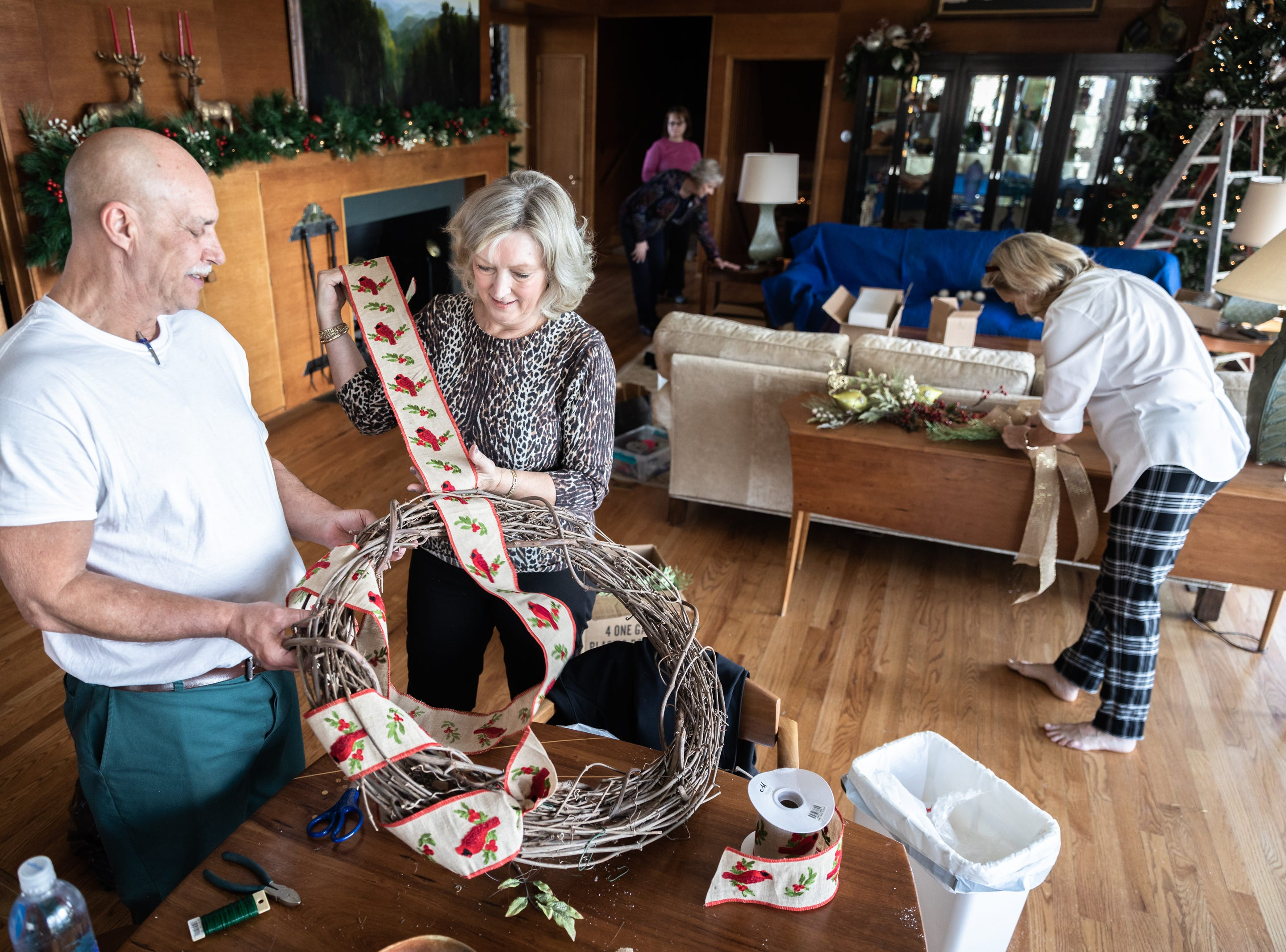 Tony Hartsell, of Asheville, and June Ray, of Waynesville, members of the Governor's Western Residence Board of Directors, work on assembling a wreath for the holidays at the residence on Patton Mountain Road in Asheville, Nov. 29, 2018.