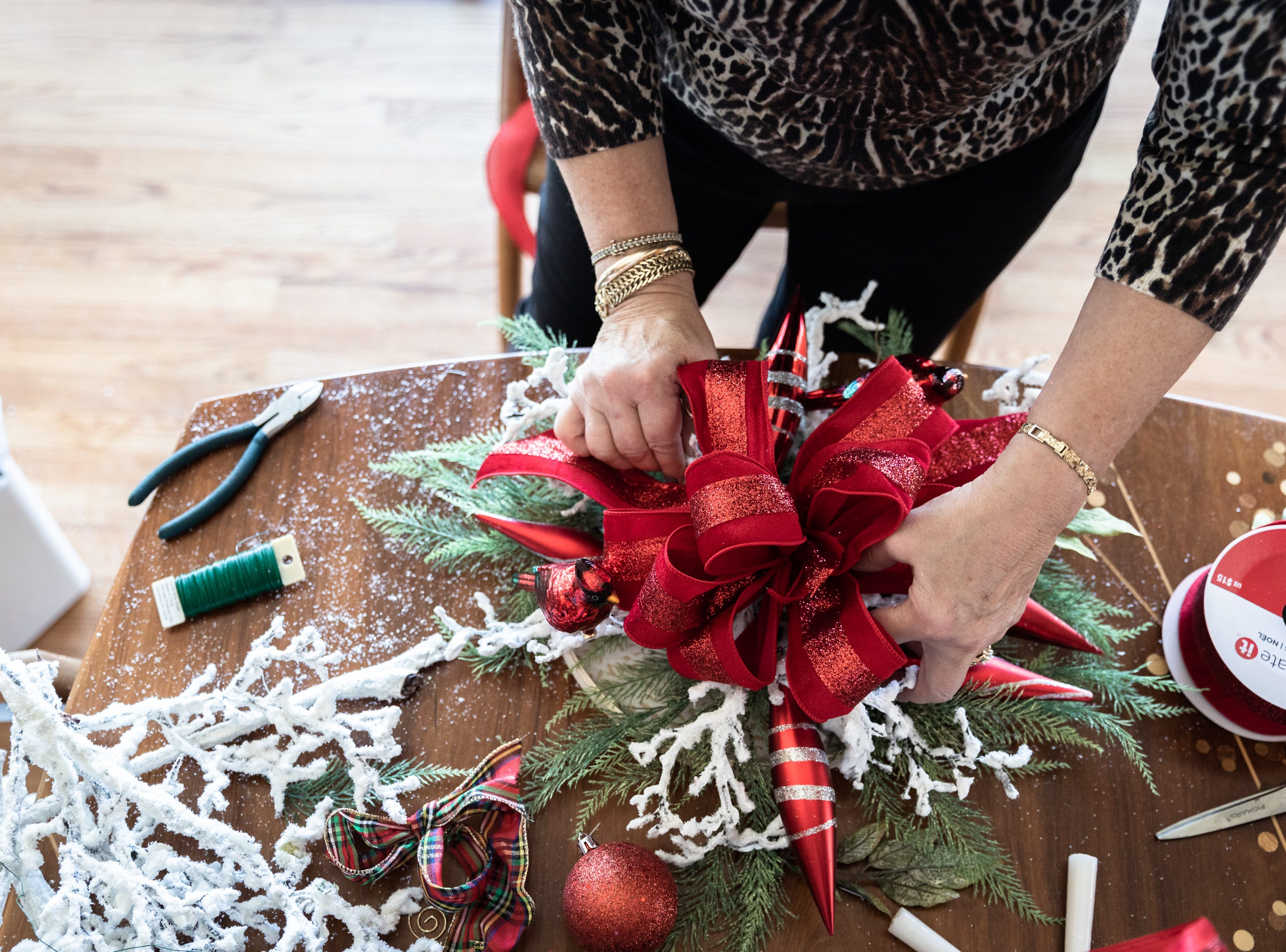 June Ray, of Waynesville, a member of the Governor's Western Residence Board of Directors, assembles a wreath for the holidays at the residence on Patton Mountain Road in Asheville, Nov. 29, 2018.