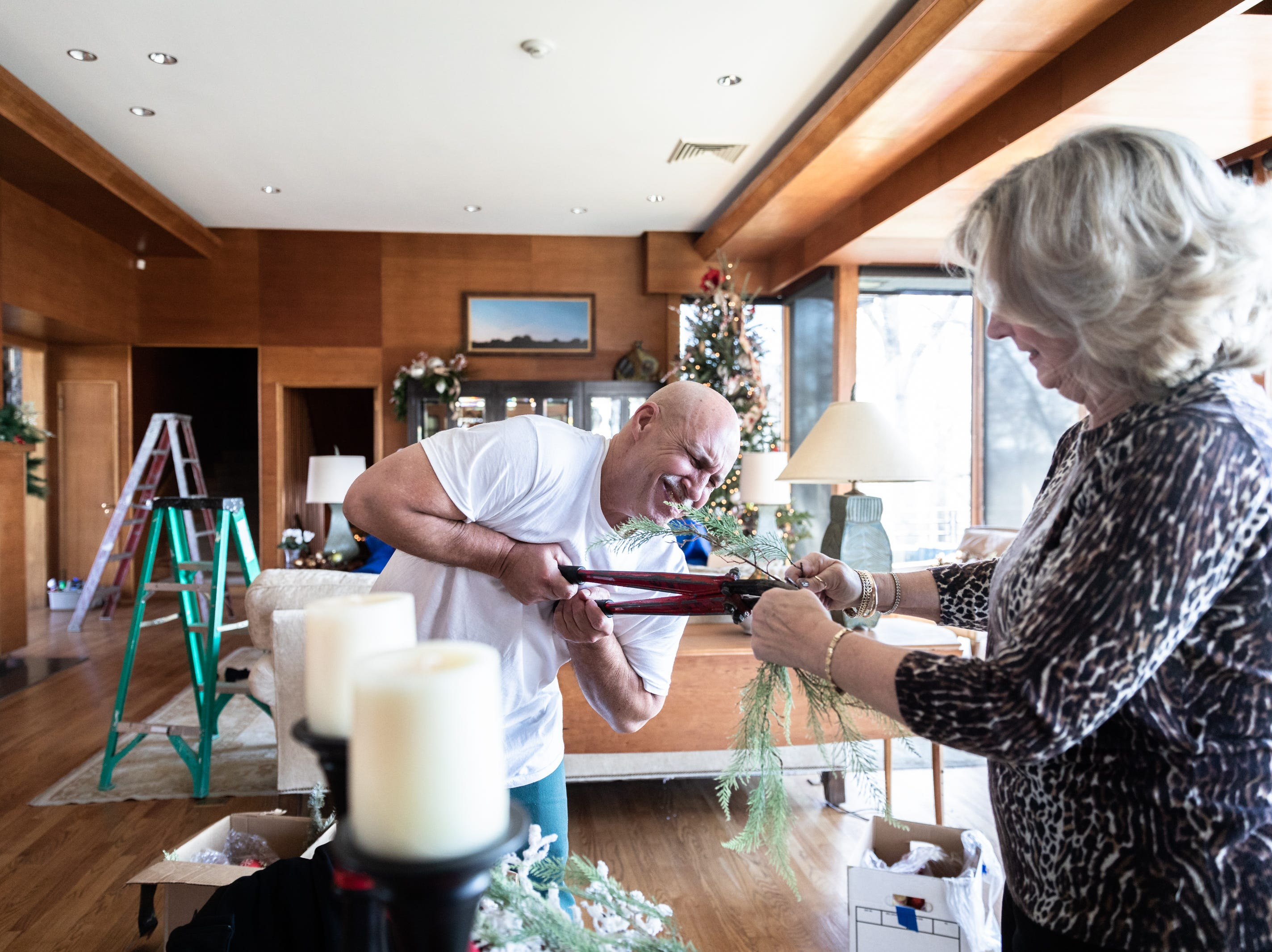 Tony Hartsell, of Asheville helps trim a decorative branch with June Ray, of Waynesville, a member of the Governor's Western Residence Board of Directors as they decorate the residence on Patton Mountain Road in Asheville, Nov. 29, 2018.
