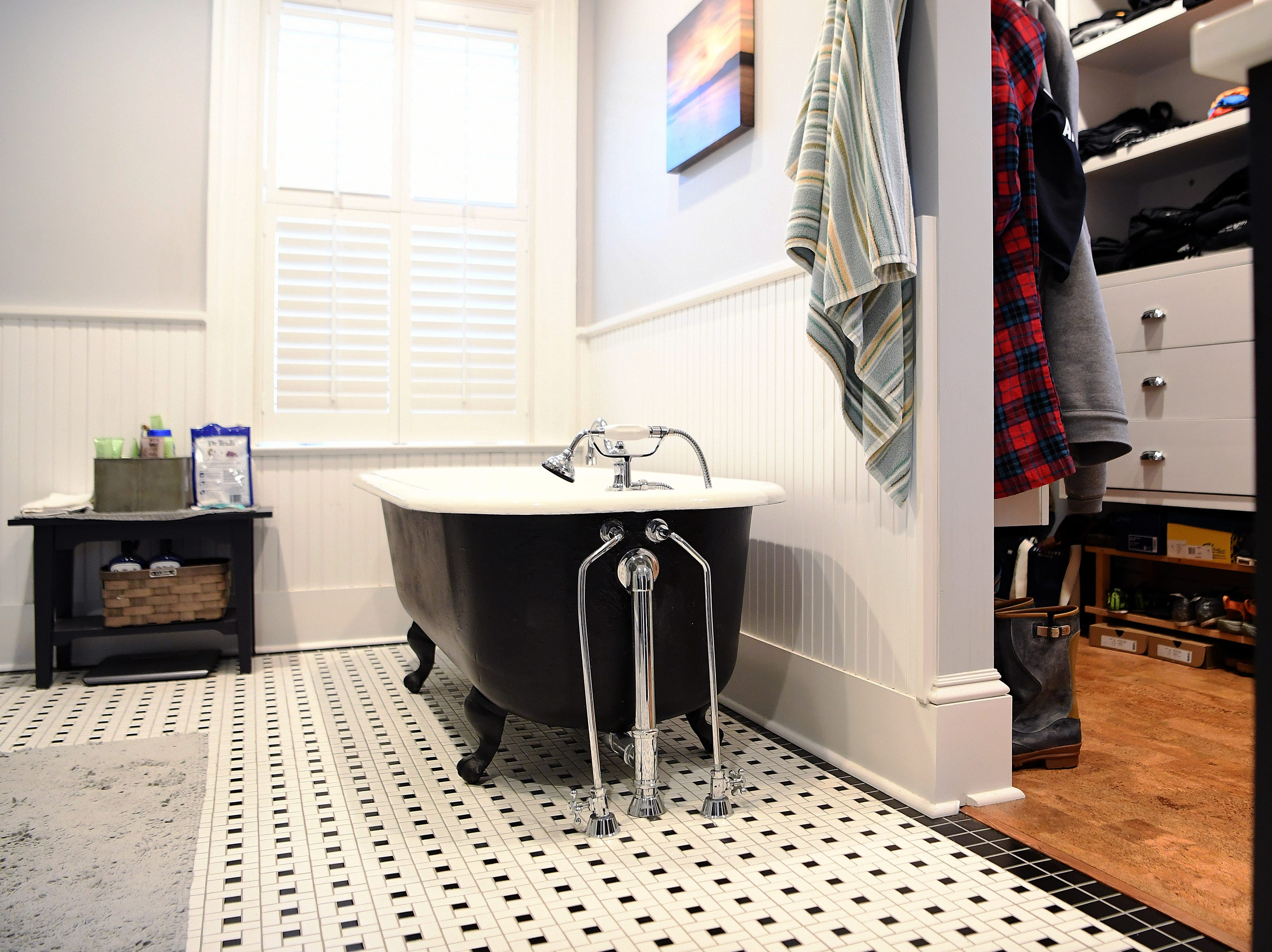 The remodel of a renters bedroom on the second floor of Linda and Marc Voorhees' Montford home became a master bath and walk-in closet. The tub, which they painted black, is original.