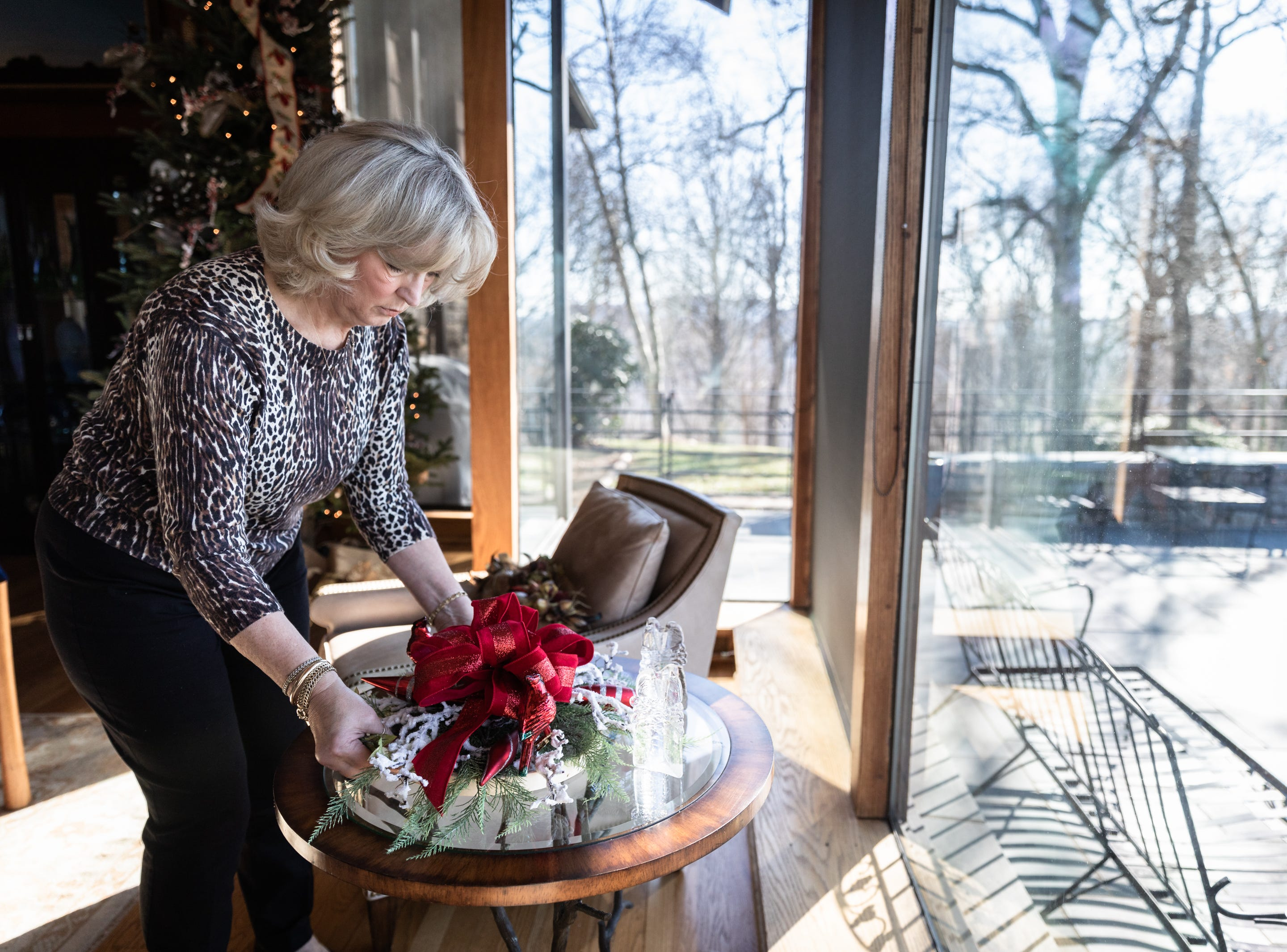 June Ray, of Waynesville, a member of the Governor's Western Residence Board of Directors, places a wreath for the holidays at the residence on Patton Mountain Road in Asheville, Nov. 29, 2018.